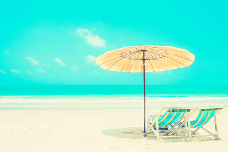 deck chairs: Blue sea and white sand beach with beach chairs and parasol, holiday and vacation concepts - vintage tone Stock Photo