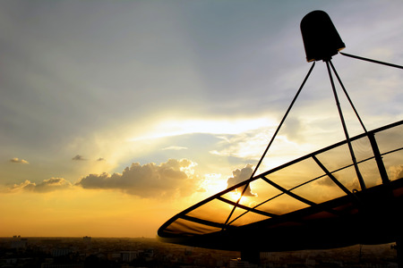 Satellite dish silhouette on twilight sky background photo