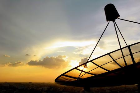 Satellite dish silhouette on twilight sky background photo