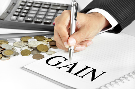 financial gains: Hand with pen  pointing to GAIN word on the paper - financial and investment concepts