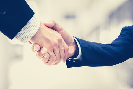 cooperation: Handshake of businessmen - vintage tone