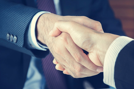 agree: Handshake of businessmen in vintage tone - greeting , dealing, merger and acquisition concepts