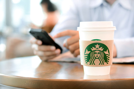 starbucks coffee: Starbucks take away coffee cup on the table with a man using smart phone and people in coffee shop as blur background  Starbucks brand is one of the most world famous coffeehouse chains from USA.