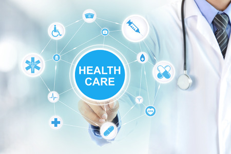 Doctor hand touching HEALTH CARE sign on virtual screen. Stock Photo