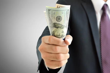 grip: Businessman hand grabbing money, US dollar (USD) bills
