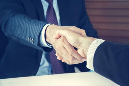 Apretón de manos de hombres de negocios en tono de época - conceptos de felicitación, de negociación, de fusiones y adquisiciones Foto de archivo