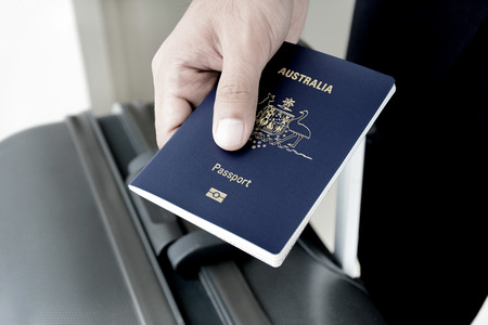 citizenship: Hands giving passport (of Australia) - dark tone