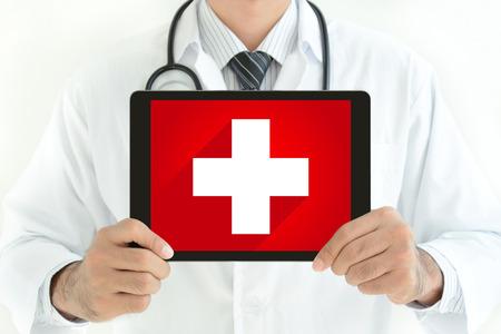s�mbolo de la medicina: Signo de primeros auxilios en la pantalla de tablet pc celebrada por el doctor Foto de archivo