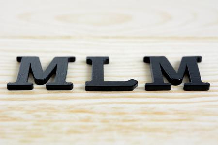 multilevel: MLM (o Multi-Level Marketing) cantare sullo sfondo di legno Archivio Fotografico