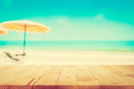 木製テーブルの上にぼやけた青い海と白い砂のビーチの背景、ビンテージ トーン - 表示に使用することができますまたは製品をモンタージュ 写真素材