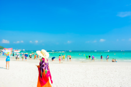 beach: Blurred people on white sand beach with blue sea an sky background