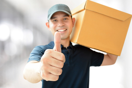 package shipment: Deliveryman carrying a parcel box, giving thumbs up