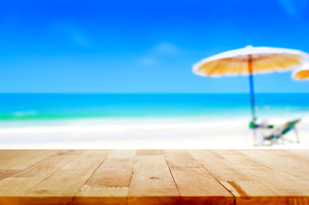 blurry: Wood table top on blurred blue sea and white sand beach background - can be used for display or montage your products Stock Photo