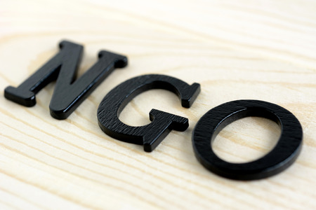 ngo: NGO letters on wood background - NGO stand for Non-Governmental Organization Stock Photo