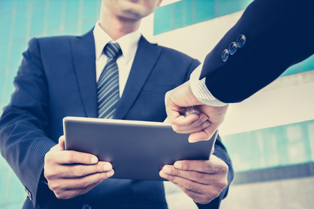 man standing: Two businessmen looking at tablet pc with one hand pointing to the screen ,business discussion concept - vintage tone, soft focus