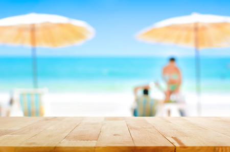 Wood table top on blurred beautiful white sand beach background with some people - can be used for montage or display your products Stock Photo