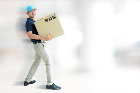 deliveryman: Deliveryman portando una scatola di cartone su sfondo grigio bianco con copia spazio Archivio Fotografico