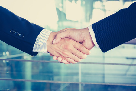 company merger: Handshake of businessmen in vintage tone, soft focus