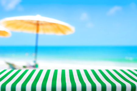 Table covered with striped tablecloth on blurred beach background - picnic and holiday concepts