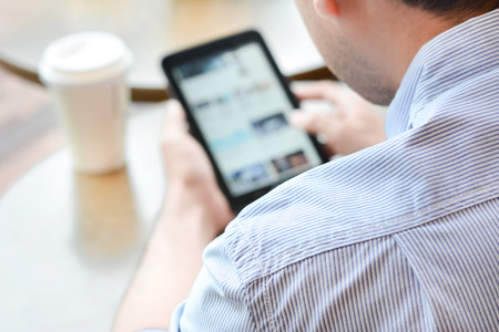 using the computer: Un hombre que usa la PC de la tableta en la cafetería con la taza de café sobre la mesa - pantalla borrosa, enfoque suave