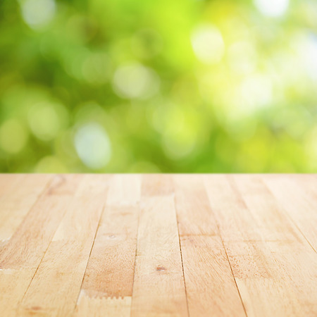 shiny background: Wood table top on green bokeh abstract background - can be used for montage or display your products
