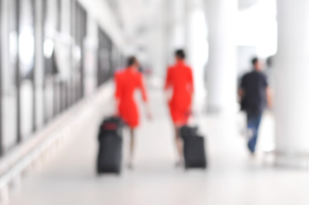 flight: Blurred people and flight attendants walking at the airport hallway