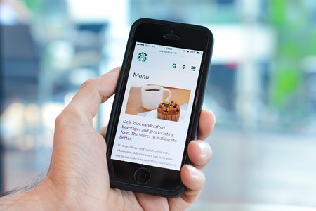 Hand holding iphone opening menu page online of Starbucks  website.