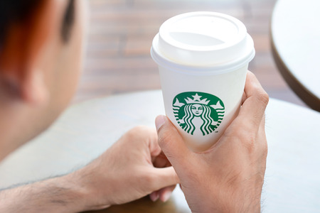 A man holding Starbucks coffee cup with brand logo. Starbucks brand is worldwide coffeehouse chains from USA. 報道画像
