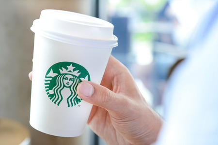 Hand holding Starbucks coffee cup with brand logo. Starbucks brand is worldwide coffeehouse chains from USA.