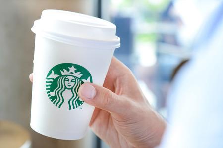 starbucks coffee: Hand holding Starbucks coffee cup with brand logo. Starbucks brand is worldwide coffeehouse chains from USA.