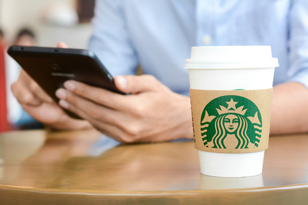 starbucks coffee: Starbucks paper coffee cup on the table with a man using tablet pc in Starbucks coffee shop. Starbucks brand is one of the most world famous coffeehouse chains from USA.