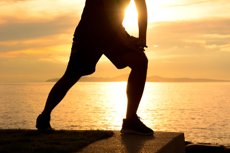lower body: Silhouette of a man lower body, stretching at the beaach in twilight