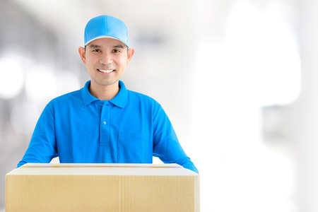 Deliveryman giving a cardboard parcel box - with copy space for text