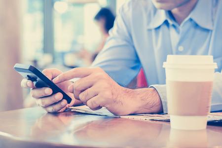 コーヒー ショップ - ビンテージ トーンでテーブルの上のコーヒー カップを持つスマート フォンを使用している人