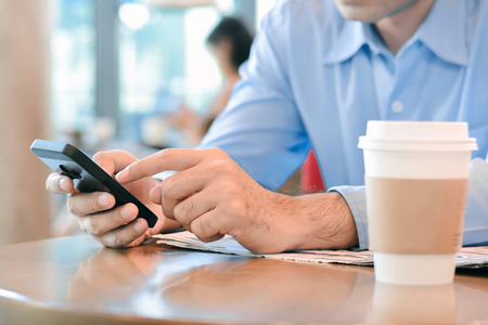 surf shop: A man using smart phone with coffee cup on the table in coffee shop