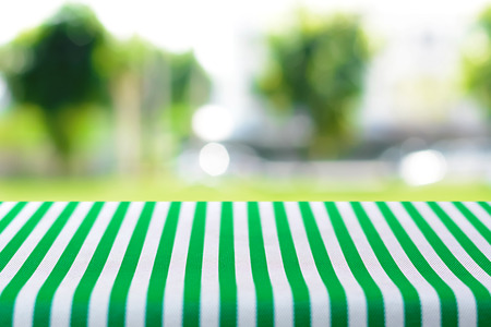 tablecloth: Table top covered with striped tablecloth on blurred green nature background - can be used for montage or display your products Stock Photo