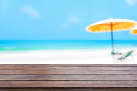 vacaciones en la playa: Antiguo oscura superficie de la mesa de madera de color marr�n sobre fondo borroso playa - se puede utilizar para la exhibici�n o montaje de sus productos Foto de archivo