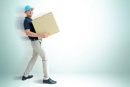 deliveryman: Deliveryman carrying a cardboard box on white gray background with copy space