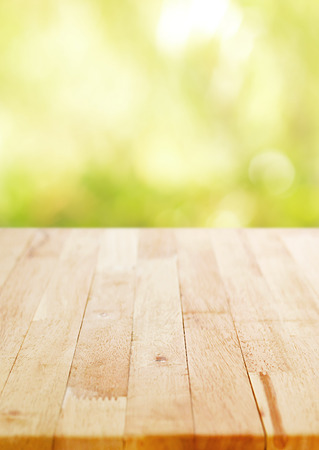 Wood table top on blur green bokeh background, poster size proportion - can be used for montage or display your products
