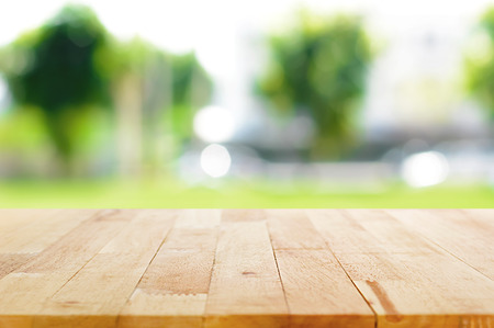 garden design: Wood table top on blurred green nature background - can be used for montage or display your products Stock Photo