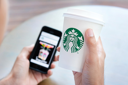 starbucks: A man holding and looking at Starbucks coffee cup while holding smart phone with another hand, in Starbucks coffee shop.