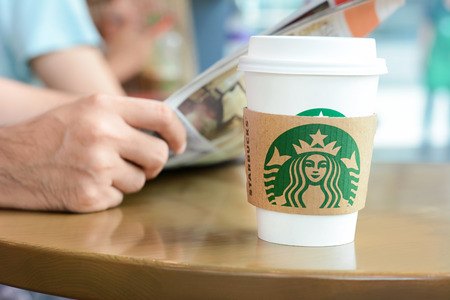 starbucks coffee: Starbucks coffee cup on the table with a man reading newspaper as background in Starbucks coffee shop. Editorial