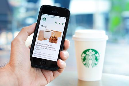 hombre tomando cafe: Mano que sostiene tel�fono inteligente abrir p�gina del men� en l�nea del sitio web de Starbucks, con el desenfoque de Starbucks taza de caf� de fondo, en la cafeter�a de Starbucks.