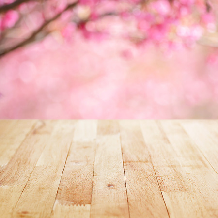 Wood table top on blurred background of pink cherry blossom flowers - can used for display or montage your products