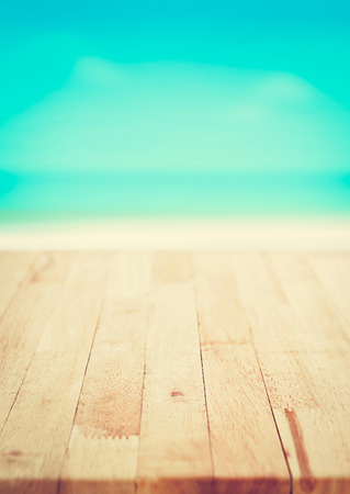 Wood table top on blur blue sea and white sand beach background, summer concept, vintage tone - poster size proportion Stock Photo