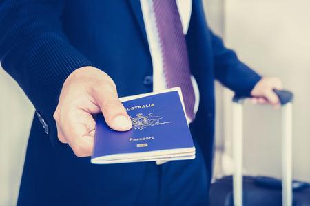 passport: Businessman giving passport with boarding  pass inside - vintage tone, soft focus