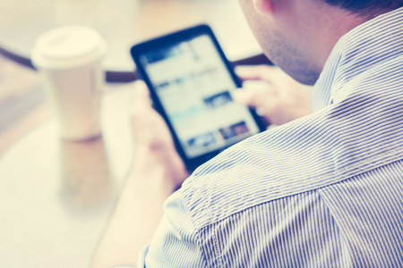 internet shop: A man using tablet pc (blurred screen) in coffee shop with coffee cup on the table - vintage tone, soft focus
