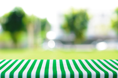 Table top covered with striped tablecloth on blurred green nature background - can be used for montage or display your products Stock Photo