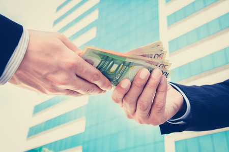 Businessman hands passing money, Euro currency (EUR) - vintage tone