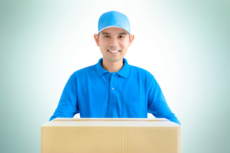 deliveryman: Deliveryman carrying a cardboard parcel box Stock Photo